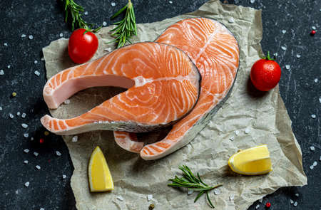Healthy food concept with two fresh raw salmon steaks, salt, peppers, lemon, tomatoes and dill on the rustic paper. salmon with tomatoes