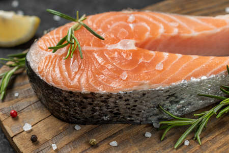 Healthy food concept Fresh salmon fillet with pepper, lemon and rosemary on a wooden rustic background 免版税图像