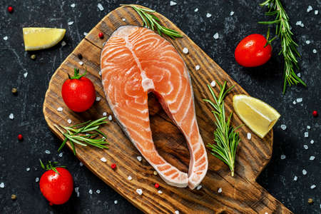 Healthy food concept. Fresh raw salmon fish steak with spices on dark wooden background. Creative layout made of fish, salmon steak top, flat lay, mockup, overhead.
