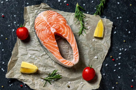 Healthy food concept. Fresh raw salmon fish steak with spices on rustik paper background. Creative layout made of fish, top view, flat lay, mockup, overhead.