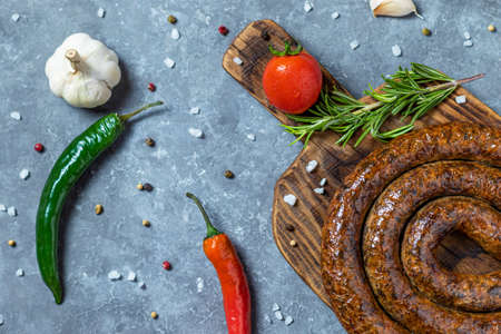 Grilled or Roasted spiral pork sausages with rosemary, salt, peper and green vegetable on plate
