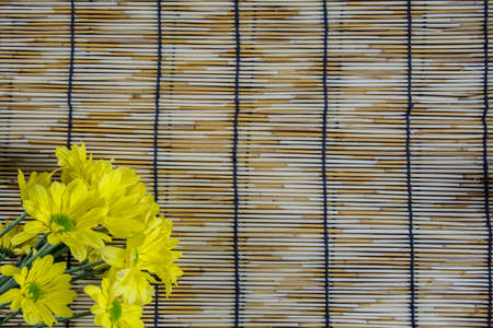 wood blinds: Yellow Flowers placed on a woven wood blinds 1 Stock Photo