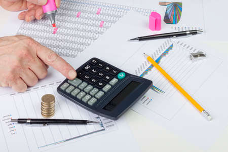 entries: Accountant balancing a sales ledger with a calculator highlighting entries Stock Photo