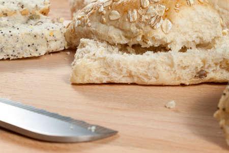 breadboard: Sliced oat flake seeded bread rolls laying on a wodden breadboard