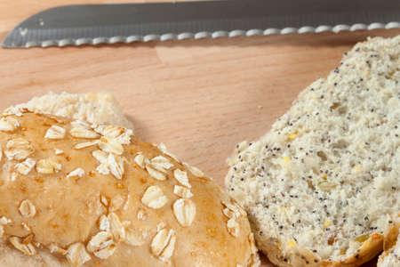 breadboard: Freshly sliced wholegrain seeded bread rolls laying on a wooden breadboard with a knife