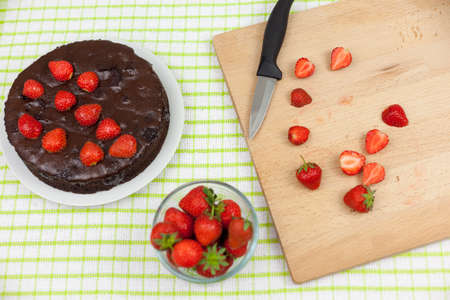 strawberrys: Plated chocolate fudge cake on a country table aside cut strawberrys on a chopping board Stock Photo