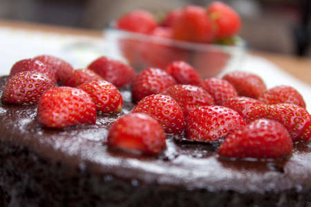 Close up of a chocolate fudge cake topped with fresh ripe strawberrys on a table Stock Photo