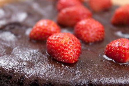 Close up of fresh ripe strawberrys topping a chocolate fudge cake