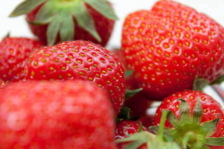 strawberrys: Close up shot of some fresh ripe strawberrys with their hulls still attached