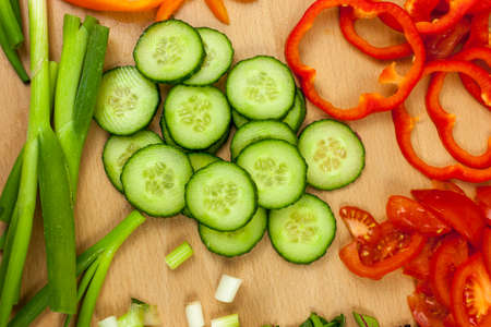 english cucumber: Freshly sliced English cucumber shot from above surrounded by other chopped vegetables