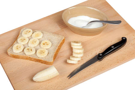 plater: Making a banana and sugar sandwich on a chopping board isolated on a pure white background