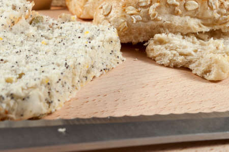 breadboard: Close up shot of a freshly sliced seeded wholegrain bread roll on a breadboard with a knife