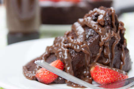 strawberrys: Plated slice of fudge cake covered in chocolate sauce with fresh ripe strawberrys Stock Photo