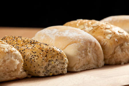 breadboard: Freshly baked and seeded wholegrain bread rolls lined up on a wooden breadboard Stock Photo