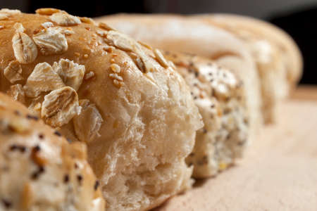 breadboard: Oatmeal and seeded wholegrain rolls lined up on a breadboard Stock Photo