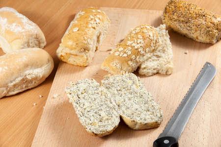 breadboard: Freshly sliced sunflower and poppy seed wholegrain bread roll on a breadboard with a knife