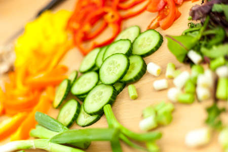english cucumber: Close bokeh shot of fresh sliced English cucumber surrounded by a selection of other chopped vegetables
