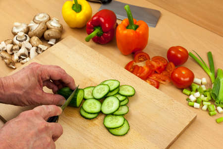 english cucumber: Close up shot of a chefs hands slicing an English cucumber on a wooden chopping board aside a selection of mixed cut vegetables Stock Photo