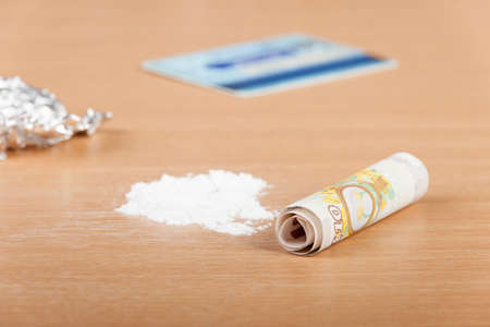 druggie: Pile of cocaine on a table ready to be lined up with a rolled up bank note and a credit card