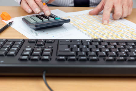 spread sheet: Financial worker busy at his desk using a calculator and checking a spread sheet Stock Photo