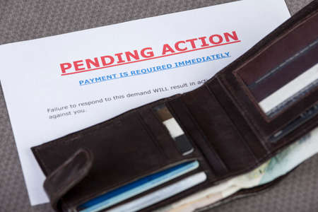 in demand: Open wallet with credit cards and cash laying across a final demand letter Stock Photo
