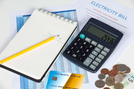 overdue: Desktop showing an overdue electricity bill with a calculator credit card and some cash