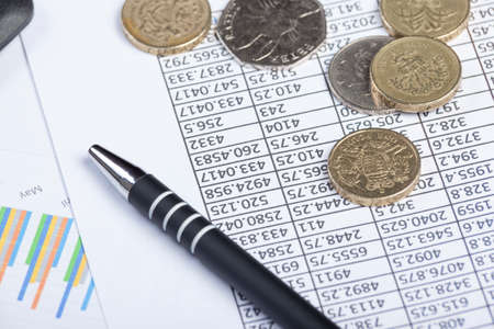 coinage: Accountants desktop with a pen and some coinage laying on top of a spread sheet amd a graph Stock Photo