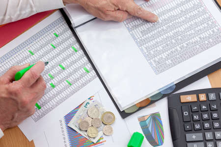 financier: Busy financier cross checking two sales reports with a calculator and some money laying on his desk