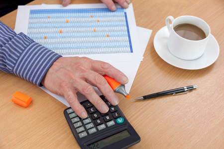 Accountant busy at his desk using a calculator to check a spreadsheet