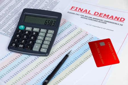 クレジット カードと電卓、およびいくつかのステートメントで机をフィナーレ督促状