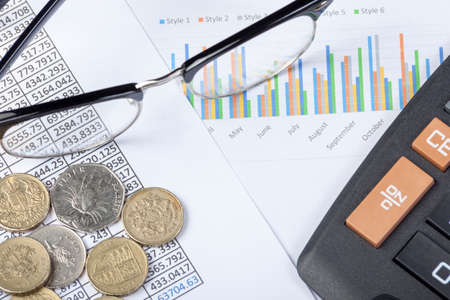 spread sheet: Pair of glasses and a calculator along with some cash lating on an accountants desk on top of a spread sheet and graph
