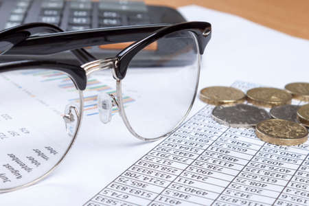 black rimmed: Close up shot of a pair of black rimmed spectacles laying on an accounts desk with some loose change and a calculator