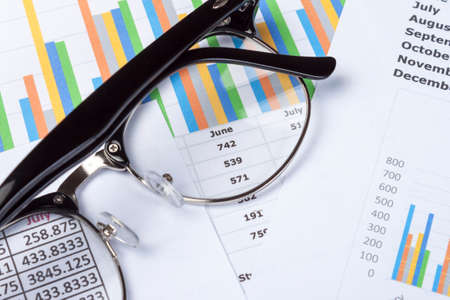 Close up shot of a pair of black rimmed specticals on top of a grapg and a spread sheet on an accountants desktop Stock Photo