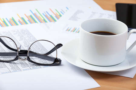 Cup of black coffee and a pair spectacles laying on an accountants desk on top of a spread sheet and some graphs