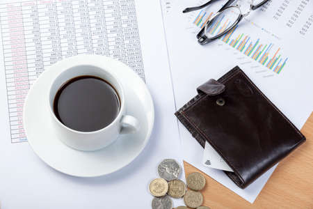 spread sheet: Wallet with a credit card in it on a accountants desk with cash and a cup of black coffee laying on top of a spread sheet a graph Stock Photo
