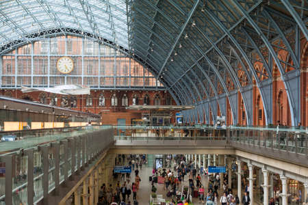 looked: LONDON, UK - JULY 26, 2016: Crowd of commuters on the lower level at St Pancras railway station over looked by the Thought of Train of Thought a creation by artist Ron Arad Editorial