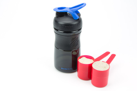 whey: Whey protein powder and plastic shaker isolated on white
