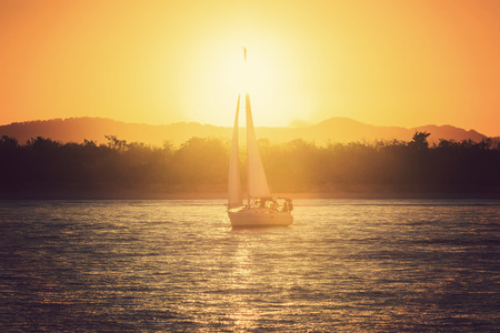 Sailing yacht against sunset photo