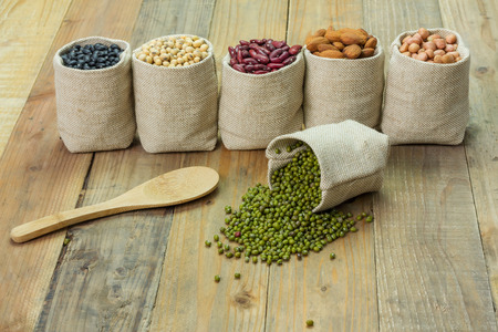 Different kinds of beans in sacks bag, focus on scattered mung beans