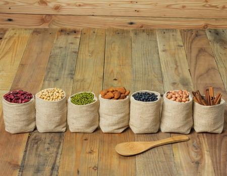 tiendas de comida: Diferentes tipos de frijoles en bolsa de sacos en el fondo de madera