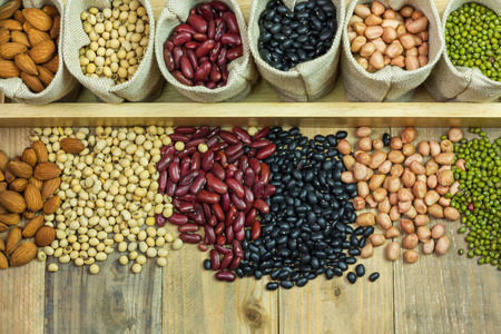 Different kinds of beans scattered on wooden background