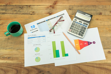 Business concept of a pencil, charts, eyeglasses, calculator, coffee cup