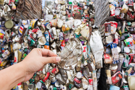 crushed aluminum cans: Hand holding aluminum can for recycle