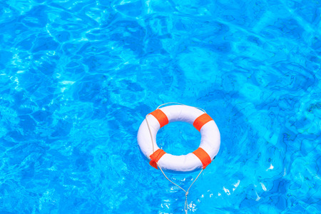 circular blue water ripple: Life buoy floating in a swimming pool Stock Photo