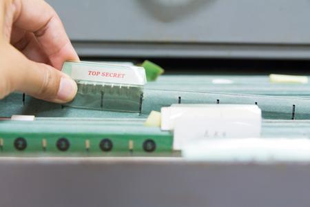 Hand holding top secret file in filing cabinet Standard-Bild