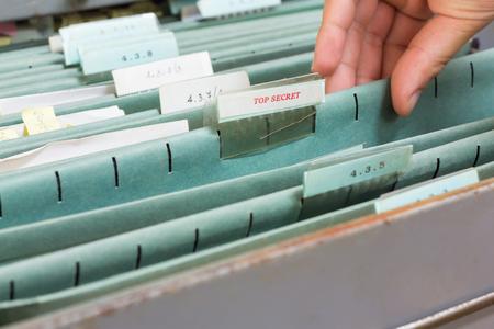 Hand holding top secret file in filing cabinet Archivio Fotografico