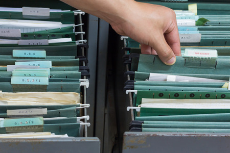 cloak and dagger: Hand holding top secret file in filing cabinet Stock Photo