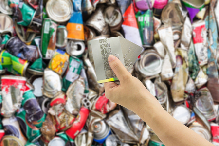 crushed cans: Woman hand holding credit card and Compressed aluminum can background Stock Photo
