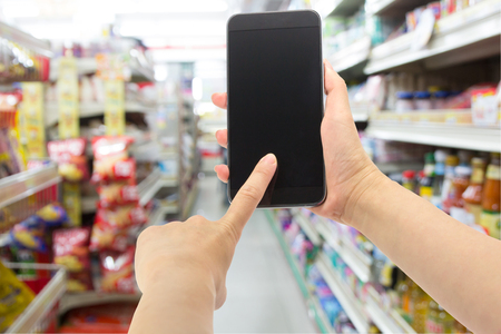 Hand holding smartphone at at convenience store