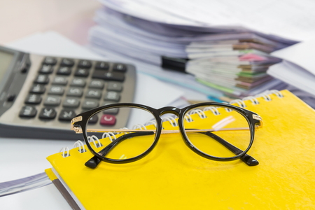 Eye glasses and Stack of business papers
